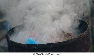Barrel of burning rubbish - Barrel of burning debris closeup