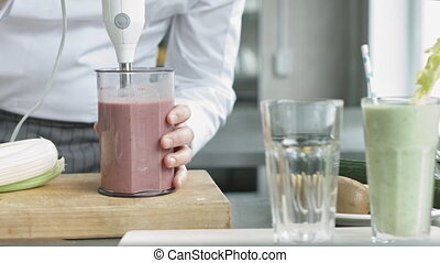 Young cook in uniform preparing smoothie - Young cook in...