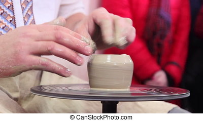Hands working on pottery wheel shaping a clay pot