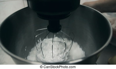 Close up: Whisks whipped egg whites and sugar in the bowl of glass