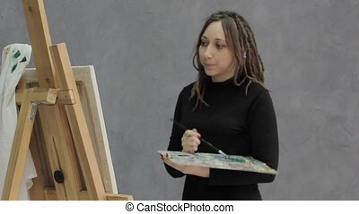 female paint artist posing next to a easel and paints on an...