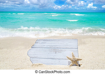 White wood board with starfish on the sandy beach - Empty...