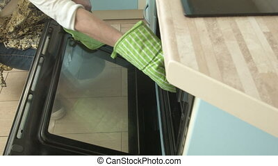 The woman takes out the oven-baked pastry and puts the tray on the stove