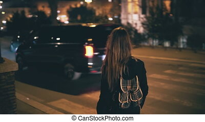 Brunette woman with backpack walking late at night....