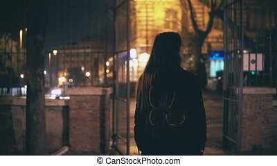 Back view of young brunette woman walking late at night in...