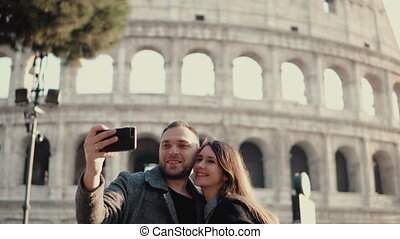 Happy young couple using smartphone for taking selfie photo...