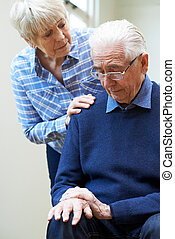 Senior Woman Comforts Husband Suffering With Parkinsons...