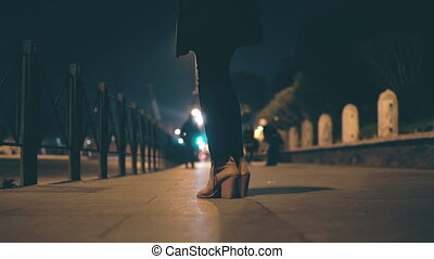 Close-up view of female legs wearing shoes on a high heel....