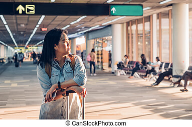 Woman traveler looking out of window and waiting with suitcases at airport departure terminal walk way to gate,Transportation travel concept