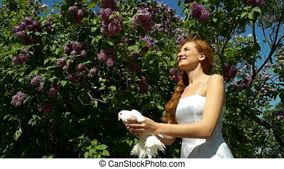 Woman Releases a Pigeon - Woman releases a white pigeon into...