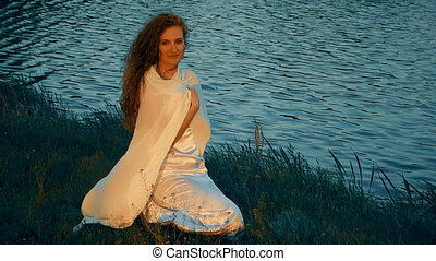 Sitting Woman in a White Dress on the River Bank