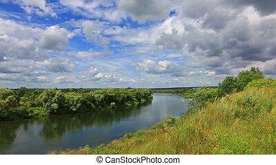 A calm river flows through the plain in a bright sunny day -...