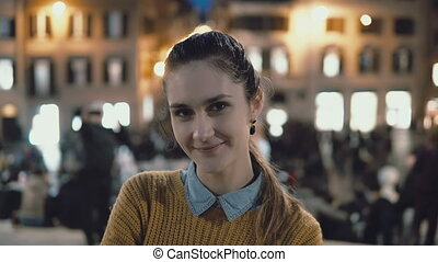 Portrait of young beautiful woman standing in the city centre in evening. Student girl looks at camera, smiling.