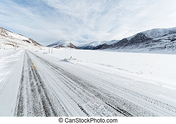 snow covered road with tibetan plateau background
