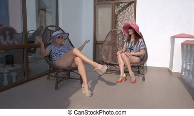 Two women relaxing in cane chairs on terrace at summer hotel...