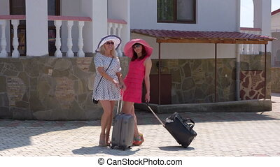 Two women tourists with rolling luggage bags arrived at...