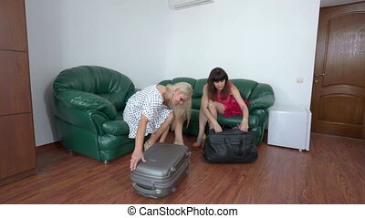 Two women tourists arrived at summer resort unpacking...