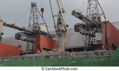 Unloading cargo ship. - Two cranes unload raw and unrefined...