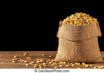 Peeled soybean in small sack on wooden table. Isolated on...