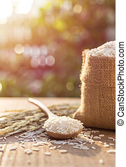 Thai jasmine rice in small sack on wooden table with...