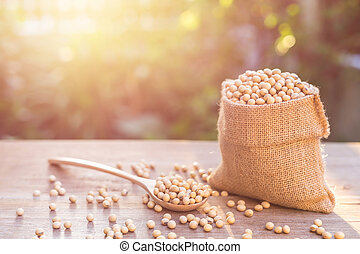 Soybean in small brown sack on wooden table. Outdoor...