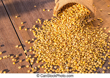 Peeled yellow soybean in small sack on wooden table...