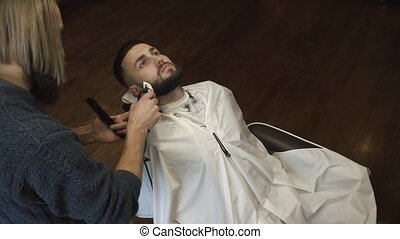 Barber shaves the beard of the client in the barbershop
