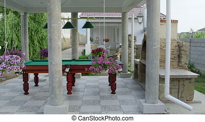 Outdoor billiard table area at back garden of a house. Two...