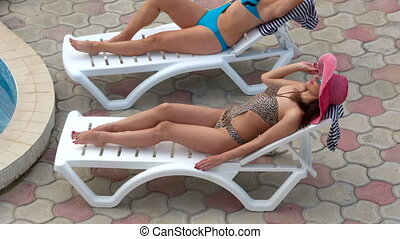 Two women relaxing on sun loungers by private pool at...