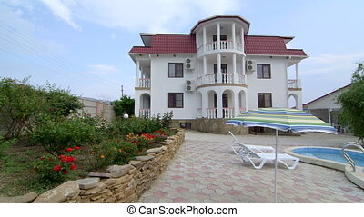 Three story house with white balustrade balcony swimming...