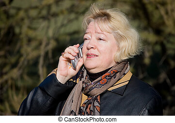 The woman talks on a cellular telephone