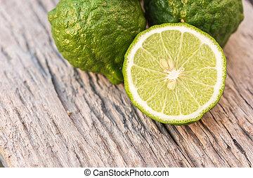 Slice green fresh Bergamot fruit on wooden table background...