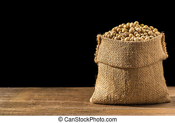 Soybean in small brown sack on wooden table. Isolated on...