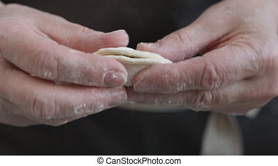 Two hands making meat dumplings. - Close-up view of two...
