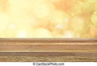 Empty wooden table in front of bokeh lights and sparkle...