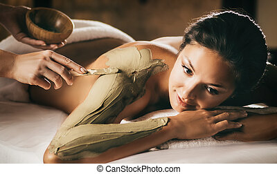 The girl enjoys mud body mask in a spa salon. Focus on the...