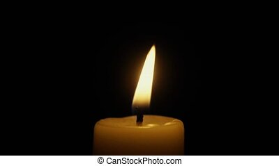 The flame of a candle swayed in the wind. Slow motion -...