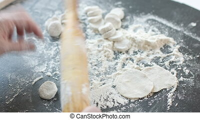 Making meat dumpling with wooden rolling pin. - Side view of...