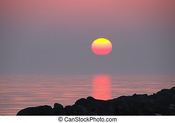 The sun draws red stripe in the water in February