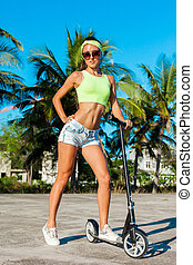 Full length portrait of tanned woman riding a scooter near palms in tropical country.