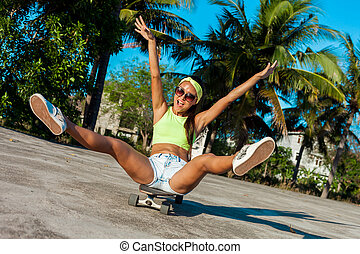 Happy attractive sexy young woman in sunglasses sitting on skateboard near palms in park.