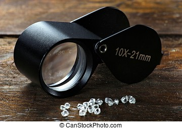 rough diamonds with folding magnifier on wooden background