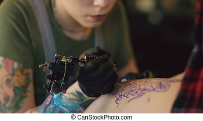 Closeup of young red haired tattoo artist woman tattooing picture on leg of client over sketch in studio indoors
