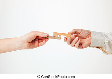 The toy wooden puzzle in hands solated on white background