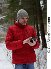 Man with tablet in forest
