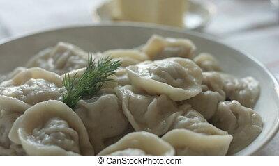 White plate of hot homemade dumplings on the table