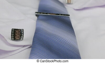 Dolly shot, focus on blue tie, cufflinks, clasp, white...