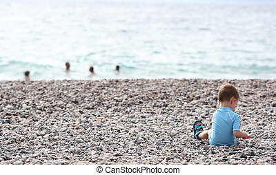 little boy playing on the beach alone while members of his...