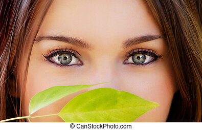 beautiful eyes - closeup of beautiful eyes and green leave...