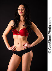 Portrait of sexy brunette woman in red and black underwear...